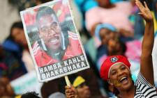 South African supporters hold a portrait of murdered Bafana Bafana captain and goalkeeper Senzo Meyiwa. Picture: AFP.