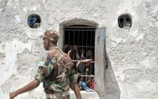 FILE: This picture released by the African Union shows a prison guard walking by a cell at the Mogadishu Central Prison, Somalia, on December 10, 2013.  Picture: AFP/AU UN IST PHOTO/Tobin Jones.