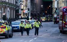 FILE: Police officers and emergency response vehicles are seen on the street outside Borough Market on 4 June 2017 the morning after a terror attack on London Bridge and the Borough area in London. Picture: AFP.
