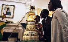 Zimbabwe President Robert Mugabe (C), flanked by his wife Grace Mugabe (L) and daughter Bona (R), blows candles on his cake during a surprise party hosted by the office of the President and Cabinet at State House in Harare, on 22 February 2016 to celebrate his 92nd birthday.  Picture: AFP