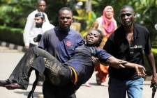 A Kenyan woman is helped to safety after masked gunmen stormed an upmarket mall and sprayed gunfire on shoppers and staff in Nairobi on 21 September 2013. Picture: AFP