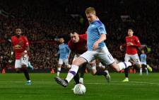 Manchester City midfielder Kevin De Bruyne strikes the ball to shoot for City's third goal during the English League Cup semifinal first leg football match between Manchester United and Manchester City at Old Trafford in Manchester, north west England on 7 January 2020. Picture: AFP