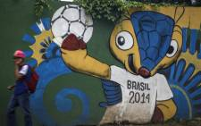 "A man passes by a wall painting with ""Fuleco, the armadillo"" - the Fifa World Cup 2014 official mascot - in Benjamin Constant street, Petropolis, south zone of Manaus, Amazonas, Brazil on 27 March, 2014. Picture: AFP."