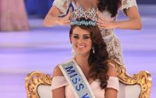 Miss World 2013 Megan Young (top) crowns Miss South Africa Rolene Strauss (bottom) as Miss World 2014 during the grand final of the Miss World 2014 pageant at the Excel London ICC Auditorium in London on 14 December, 2014. Picture: AFP