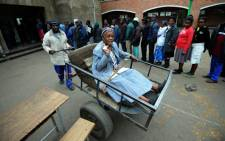Zimbawean Chizema Najika (L), 80, shows her card as she leaves in a pass cart, after voting, a polling station where other people queue up in Harare on July 31, 2013. Picture: AFP.