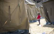 A little girl plays with a guy rope on one of the tents in the displaced foreign nationals camp in Primrose. Picture: Thomas Holder/EWN
