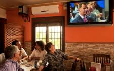 People watch a TV broadcast of Spain's King Juan Carlos announcing his abdication in favour of his son Prince Felipe, 2 June 2014. Picture: AFP.
