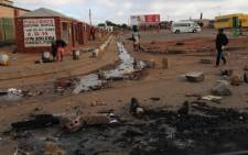 A woman walks across burnt tyres, rocks used to barricade roads during protest and sewaga spill in Bekkersdal east of Johannesburg. Picture: Sebabatso Mosamo/EWN