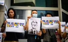 Activists holding placards - one an illustration (C) of Simon Cheng and others carrying a message using International Code of Signals (ICS) flags - gather outside the British Consulate-General building in Hong Kong on 21 August 2019. Picture: AFP