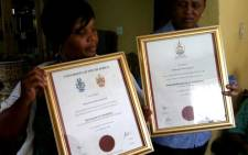 Relatives of Bonaventure Mynhard hold his Honours and BComm certificates which he achieved while in prison. Picture: Mandy Wiener/EWN