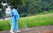 A picture taken on 24 July 2014 shows a staff member of the Christian charity Samaritan's Purse spraying product as he treats the premises outside the ELWA hospital in the Liberian capital Monrovia. Picture: AFP.