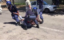 This video screengrab shows police officers draggin a Rhodes University student after firing rubber bullets at #FeesMustFall protestors on 28 September 2016.