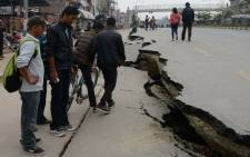 Nepalese residents walk past road damage following an earthquake in Kathmandu on 26 April, 2015. Picture: AFP.