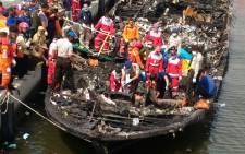 Rescuers search the charred passenger boat which was ferrying around 200 people off the coast of Jakarta to Tidung island when a fire started on the boat on January 1, 2017.  Picture: AFP