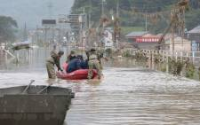 Japan Self-Defence Forces and police officers handle an inflatable boat to join rescue operations at a nursing home following heavy rain in Kuma village, Kumamoto prefecture, on 5 July 2020. Picture: AFP