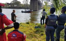 Paramedics and SA Police Service officers retrieve the body of a teenage boy who drowned in the Vaal River. Picture: ER24.