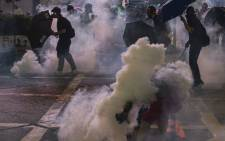Masked protesters use umbrellas as Hong Kong police fire tear gas during a pro-democracy rally in Kowloon district in Hong Kong on 20 October 2019.  Picture: AFP