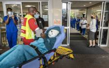 Rodwell Khomazana (C), 9, is taken into the hopsital on a gurney at the Mediclinic Sandton Hospital in Sandton on 19 June 2021. Plastic surgeons in South Africa are preparing to reconstruct the face of a Zimbabwean boy mauled by a hyena during a night time church service last month. Picture: Guillem Sartorio/AFP