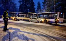 A bus of the Geneva Public Transport (TPG) is blocked with a car on a street of Geneva after a snowstorm hit western Switzerland on January 12, 2021. Picture: Fabrice Coffrini/ AFP