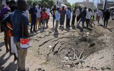 People stand next to damages at the scene of a car bombing attack in Mogadishu, Somalia, on 22 December 2018. 16 people were killed in a double car bomb attack claimed by the jihadist Shabaab group near the presidential palace in the Somali capital Mogadishu, police said. Picture: AFP.