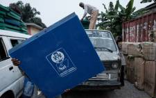 Staff members of the Independent National Electoral Commission (INEC) unload ballot boxes from a van outside their local office in Port Harcourt on 16 February 2019 after Nigeria's electoral watchdog postponed presidential and parliamentary elections. Picture: AFP.