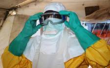 FILE: A member of Doctors Without Borders (MSF) putting on protective gear at the isolation ward of the Donka Hospital in Conakry, where people infected with the Ebola virus are being treated. Picture: AFP.