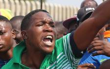 A Kya Sand resident shouts at police as hundreds of community members march through the streets surrounding the informal settlement over service delivery issues on 12 October 2015. Picture: Reinart Toerien/EWN