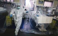 FILE: A medical staff member exits a room protected by a transparent tarpaulin after taking care of a patient infected with COVID-19 at the intensive care unit of the Franco-Britannique hospital in Levallois-Perret, northern Paris on 9 April 2020. Picture: AFP