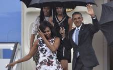 US President Barack Obama waves next to First Lady Michelle Obama and their daughters Malia and Sasha upon their arrival at Jose Marti international airport in Havana on 20 March, 2016. Picture: AFP.