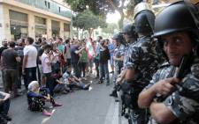 Lebanese activists stand in front of riot police outside the environment ministry in downtown Beirut on 1 September, 2015 as Lebanese police started forcefully evacuating protesters who had occupied part of the building in a surprise sit-in. Picture: AFP.