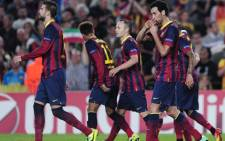 Barcelona's midfielder Sergio Busquets is congratulated by his teammates after scoring during the UEFA Champions league football match against AC Milan at the Camp Nou on 6 November, 2013. Picture:AFP