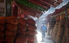 A daily labourer wearing a face mask walks in an alley at a wholesale market during a 21-day government-imposed nationwide lockdown as a preventive measure against the COVID-19 coronavirus in Kolkata, India, on 26 March 2020. Picture: AFP
