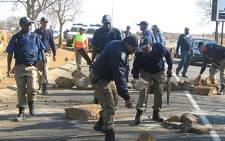 Metro police remove rocks on the road during a service delivery protest. Picture: Eyewitness News