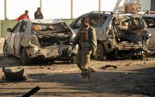 FILE: A Somali soldier walks past wrecked cars in front of the Lido seafood restaurant on January 22, 2016 following an overnight attack on the beachfront restaurant in Mogadishu.. Picture: AFP
