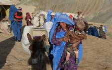 Landslide-affected Afghan villagers are pictured near the scene of the incident in Argo district in Badakhshan on May 4, 2014. Picture: AFP.