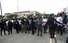 Police officers hold hands to barricade protestors to prevent people gaining entry at a government house during the ongoing demonstrations to call for the scrapping of the controversial police unit at Ikeja, Nigeria, on 9 October 2020. Picture: AFP