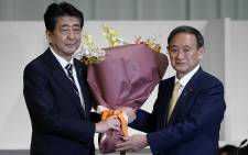 Japan's outgoing Prime Minister Shinzo Abe (L) presents new leader of Liberal Democratic Party (LDP) Yoshihide Suga (R) flowers after the latter was elected as new head of Japan's ruling party at during the leadership election in Tokyo on 14 September 2020. Picture: AFP