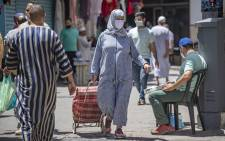 FILE: A Moroccan woman, wearing a protective face mask, walks in a street in Tangiers' Old City on 14 June 2020. Picture: AFP.