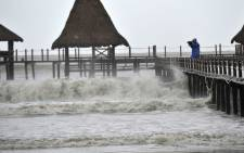 A man video graphs waves as super typhoon Rammasun hit the area in Wenchang, south China's Hainan province on 18 July, 2014. Picture: AFP.