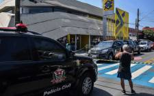 Military police vehicles remain parked outside a bank branch near a police station, shortly after security forces busted a gang trying to blow up ATM machines and shot dead at least ten robbers, in Guararema, some 80 km from Sao Paulo, Brazil on April 4, 2019. Picture: AFP.