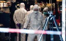Police investigator work at the area around a supermarket in the northern German city of Hamburg, where a man killed one person and wounded several others in a knife attack, on July 28, 2017. Picture: AFP.