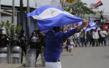 Supporters of the government (background) confront activists holding a protest against Nicaraguan President Daniel Ortega's government in Managua, on 23 September 2018. Picture: AFP.