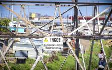 A sign warning of high electrical current, hangs redundantly on a pylon in Khayelitsha, as wires from illegal connections run around it. Picture: Thomas Holder/EWN