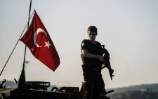 An anti-riot police officer stands guard after a military position on the Bosphorus bridge was taken over in Istanbul in Turkey. Picture: AFP.