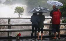 People watch the Wailuku River flood waters on the Big Island on 23 August, 2018 in Hilo, Hawaii. Hurricane Lane has brought more than a foot of rain to some parts of the Big Island which is under a flash flood warning. Picture: AFP.