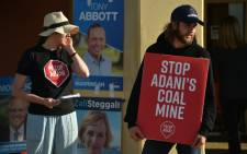 FILE: Climate change activists hold placards outside a polling station in the Liberal-held Sydney seat of Warringah during Australia's general election in Sydney on 18 May 2019. Picture: AFP
