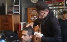Aldrid Swartz sits as Mark Hughes gives him a fresh haircut. Photo: Bertram Malgas/EWN