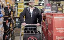 A customer buys alcohol at a liquor shop in Melville, Johannesburg, on 18 August 2020. South Africa moved into level two of a five-tier lockdown on 18 August 2020, to continue efforts to curb the spread of the COVID-19 coronavirus. Under level two, liquor and tobacco sales will resume. Picture: AFP