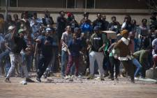 FILE: Students hurl rocks at private security at Senate House at Wits University during fees must fall protests. Picture: Nina Leslie/i-Witness.