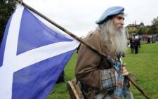 FILE: A pro-independence supporter wearing a kilt holds the Scottish flag as people gather for a rally in Edinburgh. Picture: AFP.